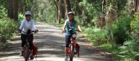 Cyclists on a dirt road leading to the Bemore Falls | Kate Baker
